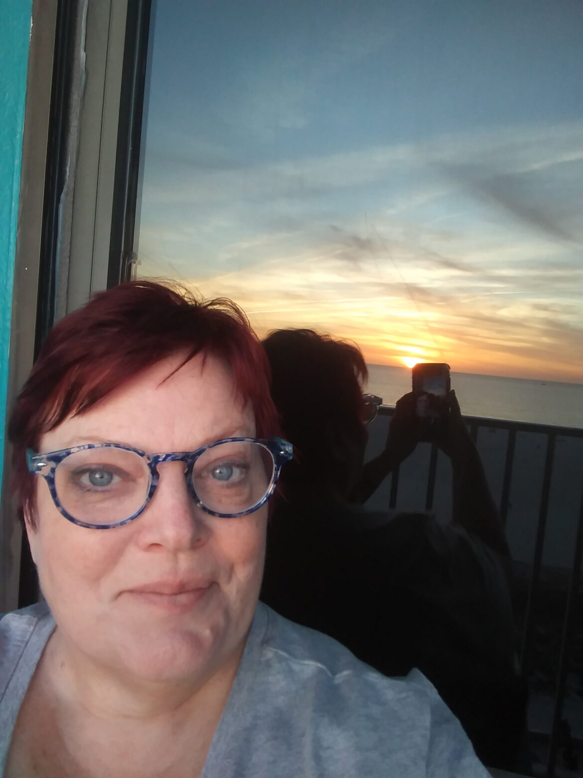 Author and editor Luanne Smith with the reflection of a sunset behind her. She is a white woman with short red hair and round blue-framed glasses.